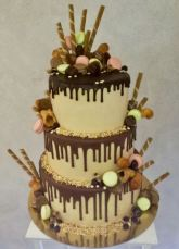 Drip Cake al cioccolato decorata con ghiaccia, macarons, dolci, cioccolatini, wafer, cannoli, granella di nocciola - Wedding cake - torta nuziale - prodotta da Gufo Bianco Cake Design Carmagnola Torino